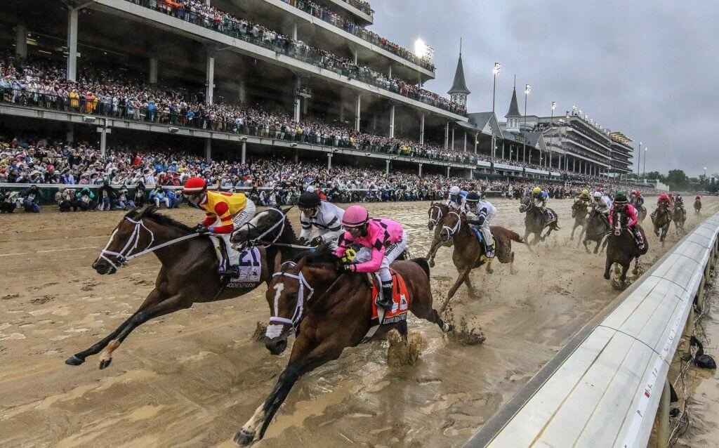 Mud is splashed up on the horses as they make their way past the grandstands at Churchill Downs for the 145th Running of the Kentucky Derby on May 4, 2019. Syndication Louisville