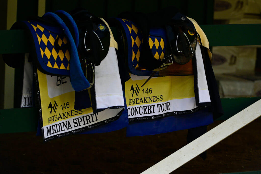 Medina Spirit and Concert Tour saddle s hang in the on a railing at Pimlico Race Course.